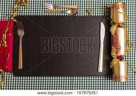 Place laid for Xmas dinner knife fork Christmas cracker napkin on slate mat.