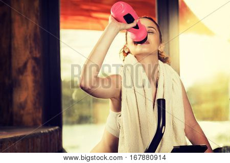 Active Young Woman Doing Exercise On Bicycle At Home. Woman Drin