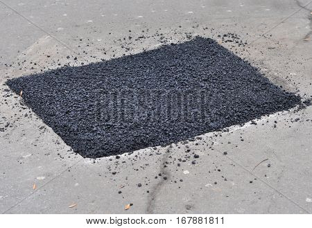 Close up on asphalt road repair. Repair pavement and laying new asphalt patching method outdoors.