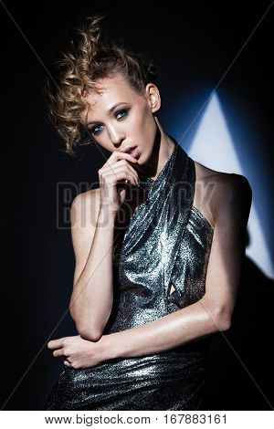 creative hairstyle and makeup concept - young fashion model posing in a spot of theatrical dramatic light