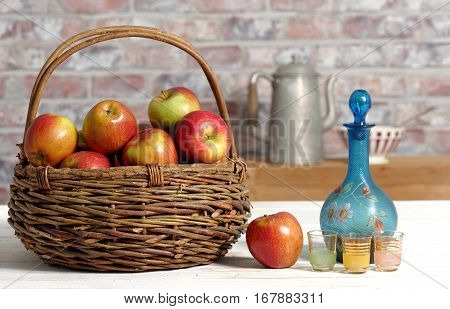Basket with beautiful apples and carafe of calvados