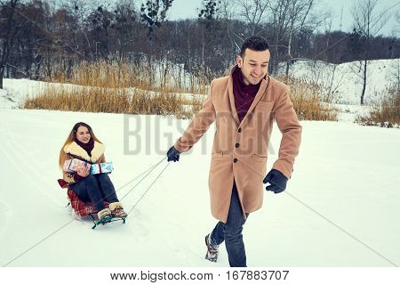 А young couple dressed in coats and scarves go sledging