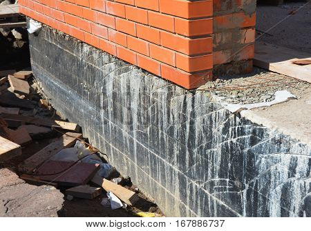 Waterproofing foundation walls. Foundation Waterproofing and Damp proofing Coatings.Waterproofing house foundation with spray on tar. House insulation waterproofing basement and foundations