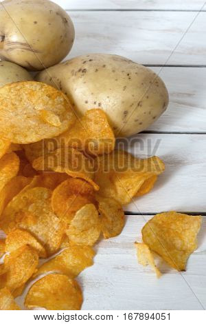 Fresh raw potatoes and chips with spice on a white wooden background