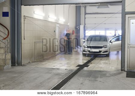 Servicemen (he is blurred) washes an automobile in a car wash