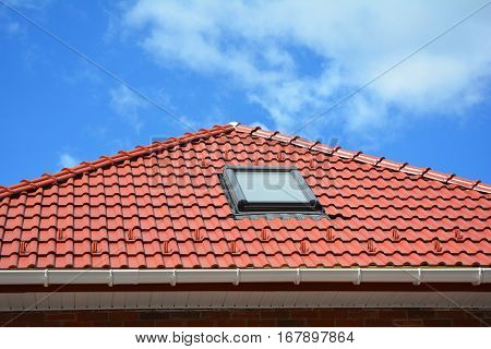 Skylight on red ceramic tiles house roof with rain gutter. Skylights Roof Windows and Sun Tunnels. Attic skylight solution outdoor.