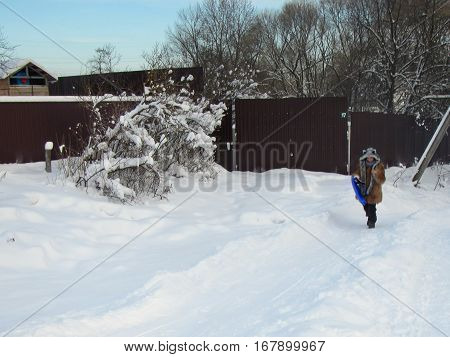 Winter Fun Concept. Russian snowy Winter landscape with village, small hill and girl with funny hat