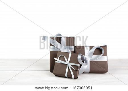 Group of gift boxes wrapped with paper and silver satin ribbon on wood isolated on white background. Modern presents for any holiday, christmas, valentine or birthday
