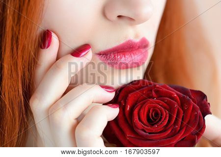 Portrait With Red Rose Flower. Dark Red Lips And Nails. Beautiful Red-haired Young Woman.