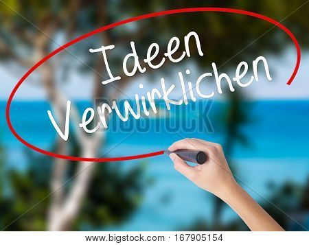 Woman Hand Writing Ideen Verwirklichen ( Realize Ideas In German) With Black Marker On Visual Screen
