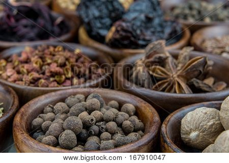 Allspice Berries Among Other Spices in small brown bowls