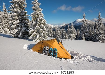 Yellow Tent And Snowshoes Standing Side By Side