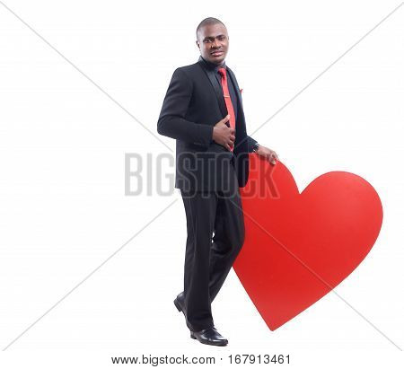 Full lenght portrait of young african man in black suite and red tie leaning on big decorated red heart at studio, seriously looking and posing at camera. Gift for Valentine Day. White background.