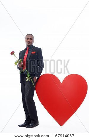 Young handsome african man holding red rose, flower for his girlfriend for Valentine Day. Male in black suite and red tie posing and leaning of big red heart at studio. White background.