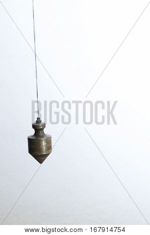 Metal plummet in the form of a cone hanged on a rope. Image is square and the gray object.