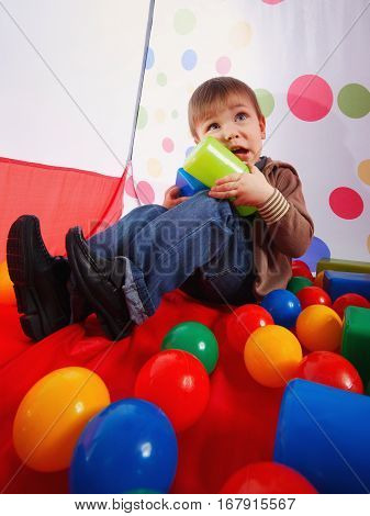 little boy playing in tent with colorful balls