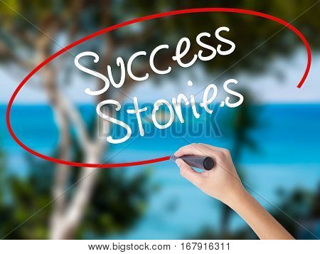 Woman Hand Writing Success Stories With Black Marker On Visual Screen