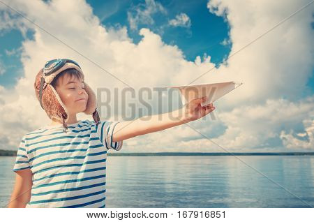boy playing with a paper plane in aviator hat. Child on the sea in summer