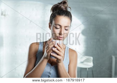 Young woman enjoying morning tea eyes closed.