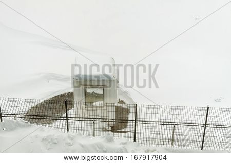 Isolated guard cabin in a building parking after massive snowfall