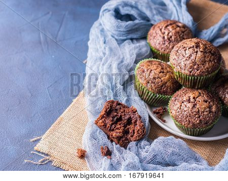 Chocolate banana muffins with sugar topping on dark blue background. Home made single portion snack. Winter baked dessert