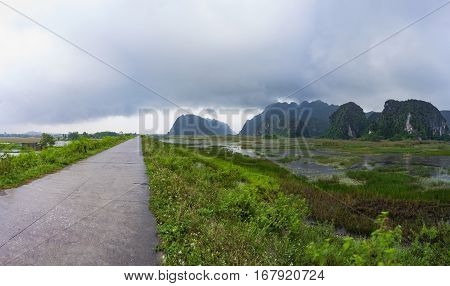 Heavy rain clouds drift across Van Long lagoon and dike Ninh Binh Vietnam