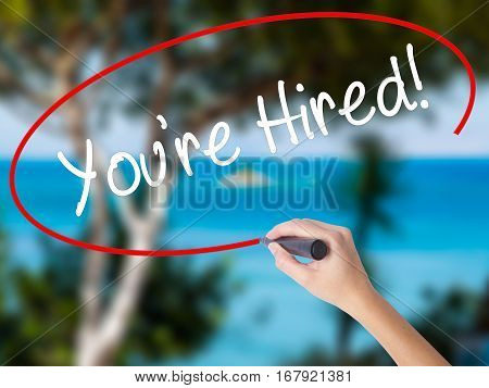 Woman Hand Writing You're Hired! With Black Marker On Visual Screen
