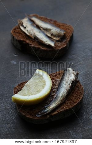 Snacks With Sardines On Black Rye Sliced Bread. Riga Traditional Delicious Dish. Smoked Sprats On Da