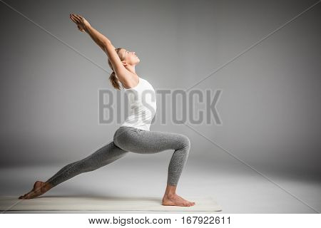 Woman practicing yoga standing in variation of Warrior I posture or Virabhadrasana One pose