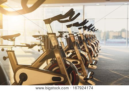 Modern gym interior with equipment. Fitness club with row of training exercise bikes in evening backlight. Healthy lifestyle concept