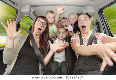 Crazy family taking a selfie and going to holidays. Group of people enjoying life in a car. Free time and transportation theme.