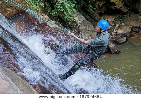 Beaufort,Sabah,Malaysia-Jan 28,2017:An Adventurer man rapels with a rope over a waterfall in Beaufort,Sabah,Borneo.Waterfall Abseiling activity adventure getting famous in Sabah,Malaysia