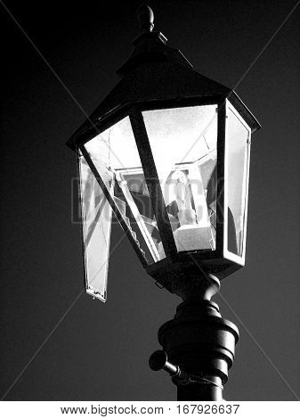 Broken hooligans street lamp in black and white. Streetlight as a symbol of vandalism. Dark colors give a gloomy, mournful mood and mystery. Vertical location.