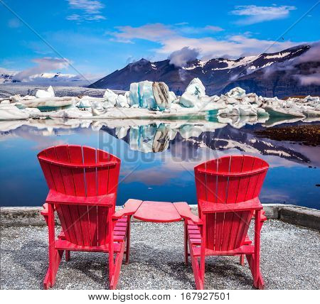 Two red deck chairs for admiring drift ice - Jokulsarlon. The concept of extreme northern tourism in Ice Lagoon, Iceland