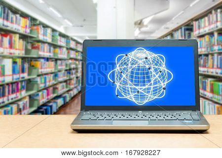 Laptop with blank screen on table with blur bookshelf at libraly Education and technology concept.