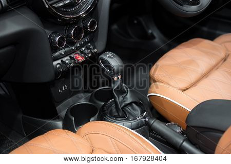 Orange luxury car Interior with steering wheel shift lever and air condition and radio button control in car.