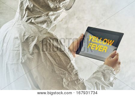 Medical scientist using tablet computer to get informed about yellow fever disease