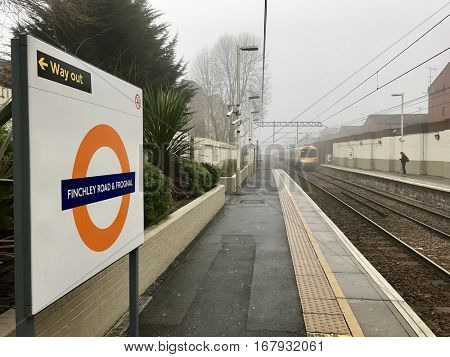 LONDON - JANUARY 23, 2017: A London Overground Train approaches the Eastbound platform at Finchley Road & Frognal Station in morning fog in North London, UK.