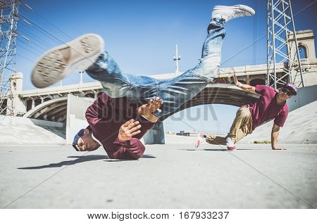 Breakdancers performing in a water duct in Los angeles