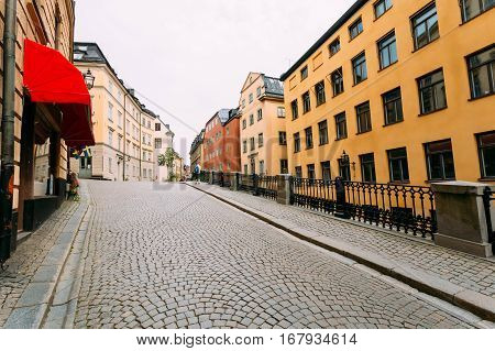 Street Paved With Paving Stones In Stockholm, Sweden. Colorful Houses.