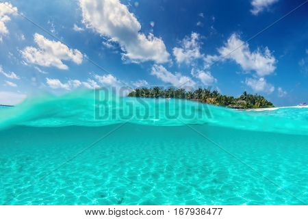 Tropical island on Indian Ocean, Maldives. Half underwater shot, clear turquoise water