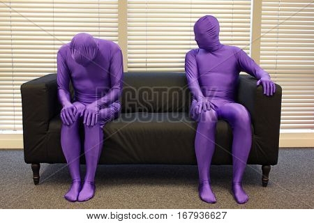 depression.anonymous men in full body elastic suits sitting on sofa in office space. one is crooked,depressed, another is observing him.