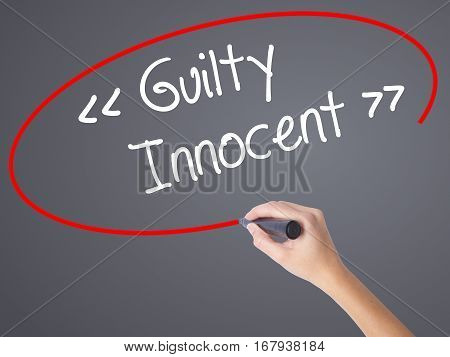 Woman Hand Writing Guilty - Innocent With Black Marker On Visual Screen.