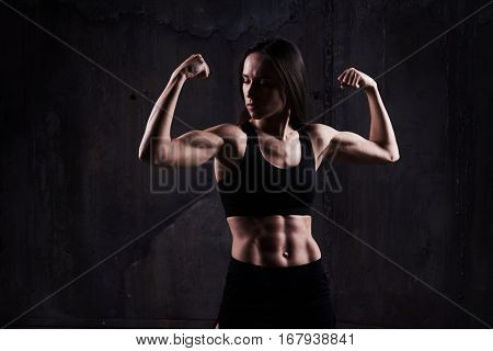 Close-up shot of good-looking powerful woman flexing biceps isolated over rusty background. Fitness model accomplishing an intense biceps work out