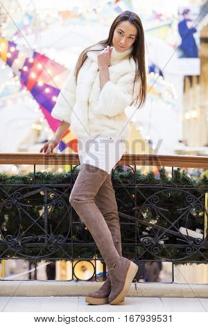 Young beautiful woman in stylish white mink coat, indoor shop