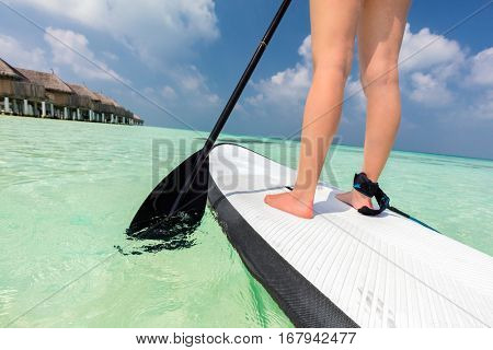 Woman does stand up paddle boarding on the ocean in Maldives. Light water sport on vacation