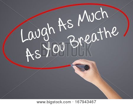 Woman Hand Writing Laugh As Much As You Breathe With Black Marker On Visual Screen.
