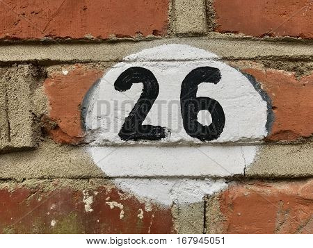 Number 26 black and white painted house address sign on red brick wall textured background