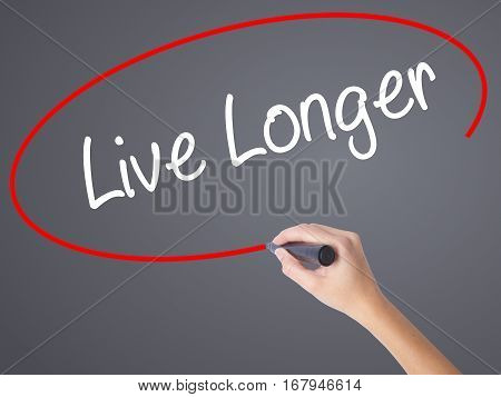 Woman Hand Writing Live Longer With Black Marker On Visual Screen