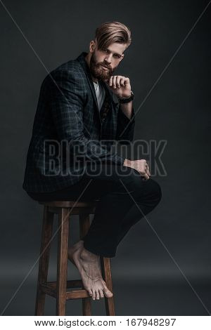 Stylish and handsome. Full length of attractive young man looking at camera and holding hand on chin while sitting on chair against grey background